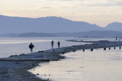 People running along Sidney Spit, Gulf Islands National Park Reserve of Canada