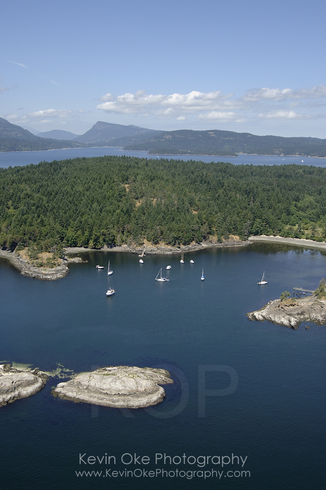 Tortoise Islets at the entrance to the anchorage at Princess Bay on Portland Island. Salt Spring Island is in the background. Gulf Islands National Park, Gulf Islands, British Columbia, Canada.