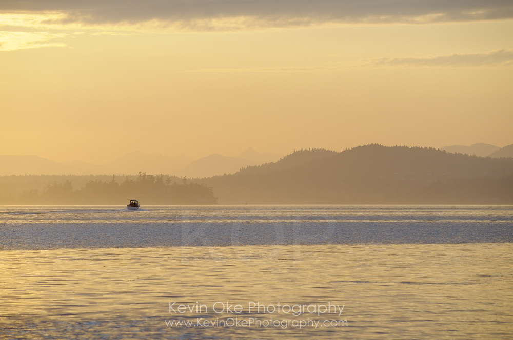 Motorboat heading into the sunset with yellowed layered islands in the background