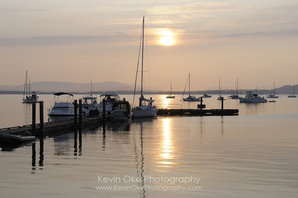 Pleasure boats at the dock in front of the sun, Sidney Spit, Gulf Islands National Park Reserve of Canada