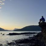 Man watching kayakers at sunset, Russell Island, British Columbia, Canada