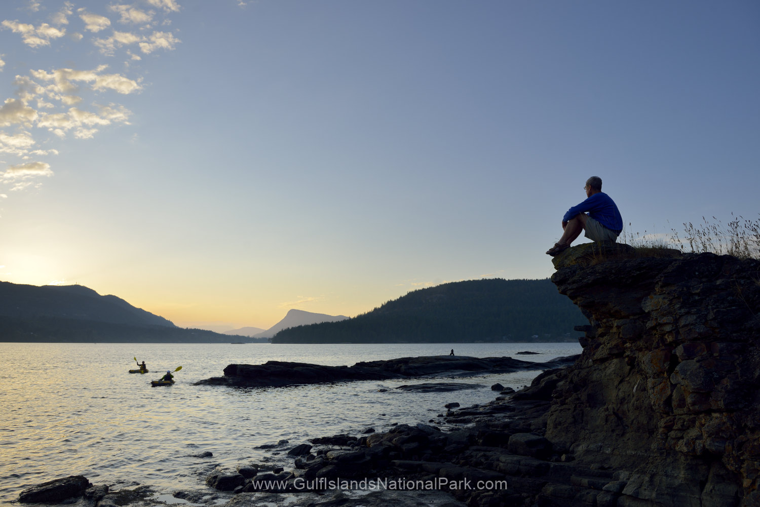 Man watching kayakers at sunset, Russell Island, British Columbia, Canada